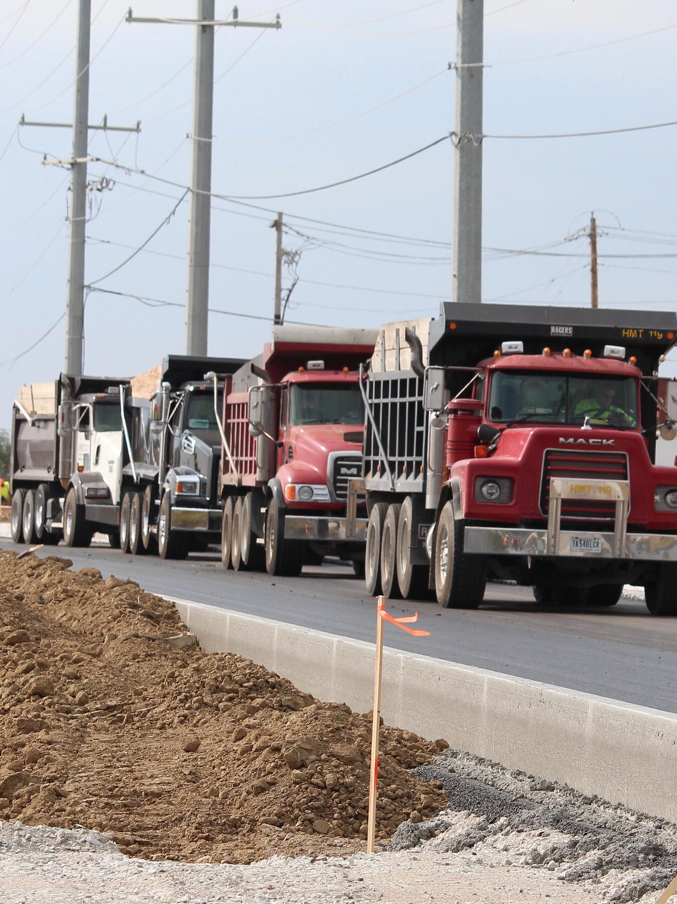trucks moving dirt on the road